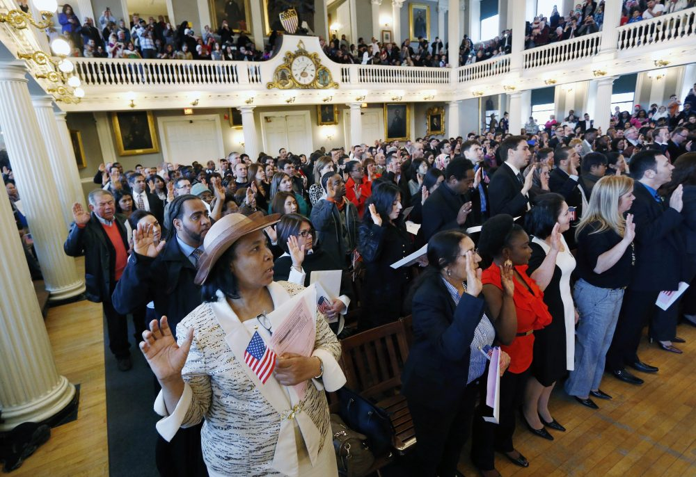Gina Dominique, lower left, who came from Haiti, takes the oath of U.S. citizenship during a naturalization ceremony in Boston, Thursday, April 2, 2015. Nearly 400 people from dozens of countries ranging from Albania to Zimbabwe took part in the ceremony. (Michael Dwyer/AP)