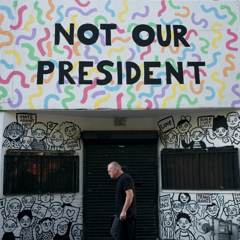 "Reports of the death of identity politics have been greatly exaggerated, writes Susan E. Reed. Pictured: A man walks past a building with the phrase ""Not Our President"" written on the facade to protest against President-elect Donald Trump Thursday, Dec. 8, 2016, in Los Angeles. (Jae C. Hong/AP)"