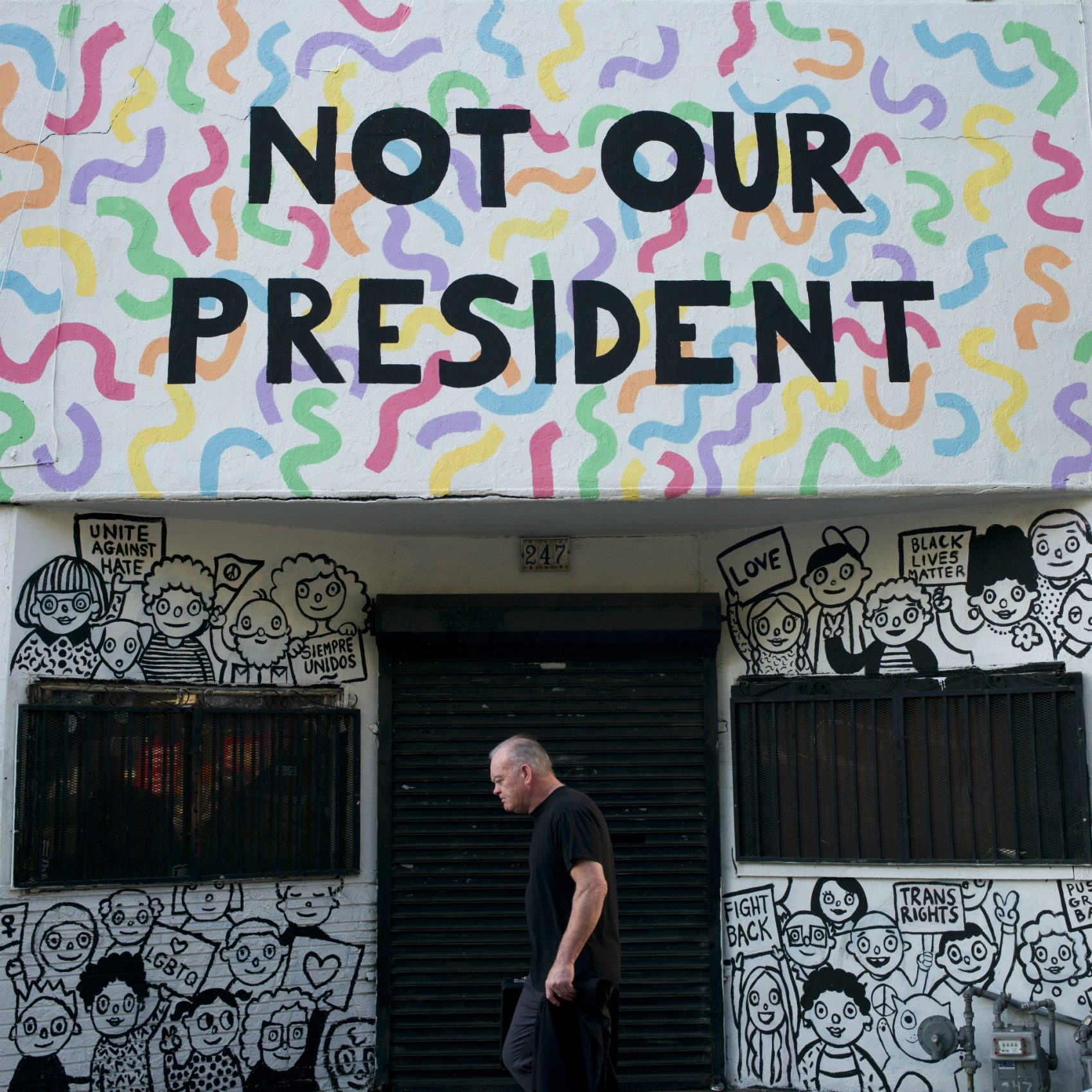 """Reports of the death of identity politics have been greatly exaggerated, writes Susan E. Reed. Pictured: A man walks past a building with the phrase """"Not Our President"""" written on the facade to protest against President-elect Donald Trump Thursday, Dec. 8, 2016, in Los Angeles. (Jae C. Hong/AP)"""