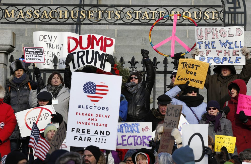 Protesters gather outside the Statehouse in Boston ahead of Massachusetts' Electoral College vote, Monday, Dec. 19, 2016. (Michael Dwyer/AP)