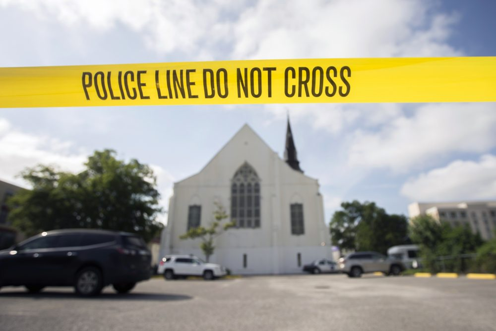 In this June 19, 2015, file photo, police tape surrounds the parking lot behind the Emanuel AME Church as FBI forensic experts work the crime scene, where nine people where shot by Dylann Storm Roof, in Charleston, S.C. (Stephen B. Morton/AP)