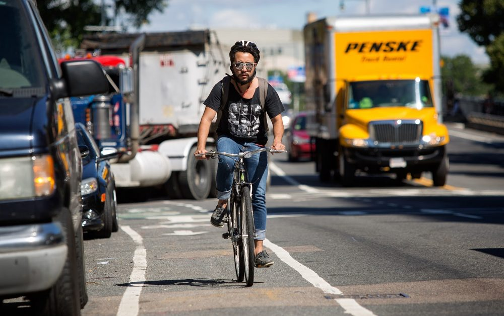 A bicyclist rides down the bike lane on Massachusetts Avenue in Boston. (Robin Lubbock/WBUR)