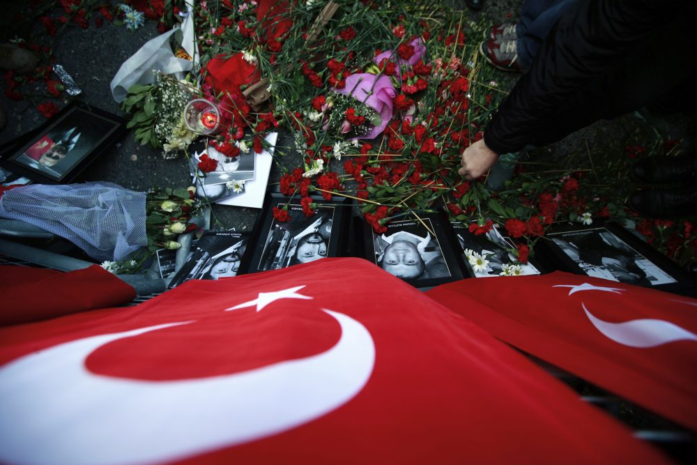 A man leaves carnations at the scene as people protest against the attack and in memorial to the victims of the nightclub New Year's Day attack, in Istanbul, Tuesday, Jan. 3, 2017. (Emrah Gurel/AP)