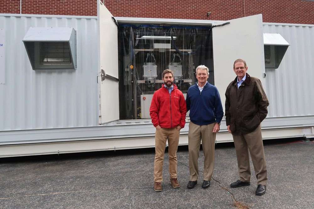 McNeely, CEO David Vieau and Director of Business Development Jonathan Milley stand in front of the Vionx Energy vanadium redox flow battery. (Bruce Gellerman/WBUR)