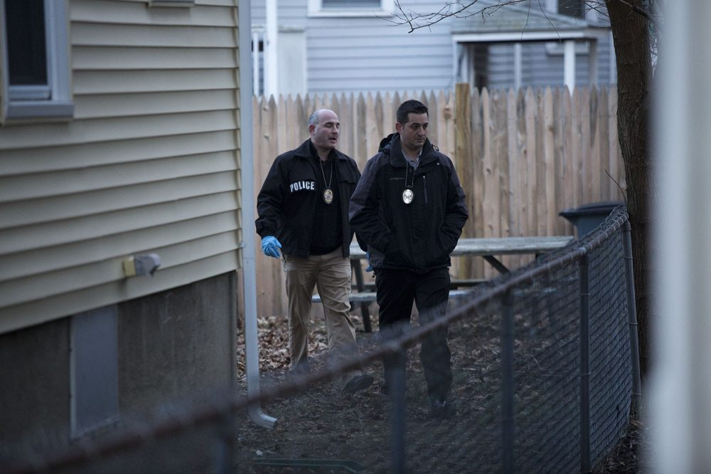 Somerville detectives examine the area where fugitive James Morales was captured, in the backyard of 85 Wheatland St. (Jesse Costa/WBUR)