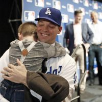 Los Angeles Dodgers pitcher Rich Hill hugs his son Brice Hill after signing  a 3- d30b6663d
