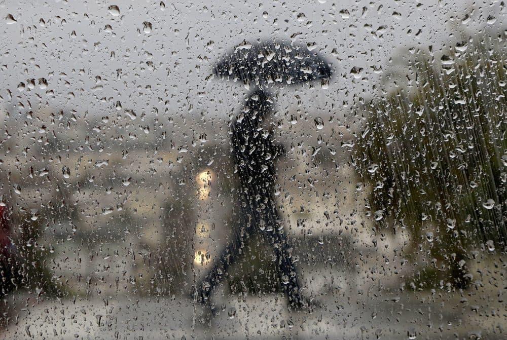 Raindrops appear on a window as a man crosses a street in San Francisco, Wednesday, Jan. 4, 2017. (Jeff Chiu/AP)