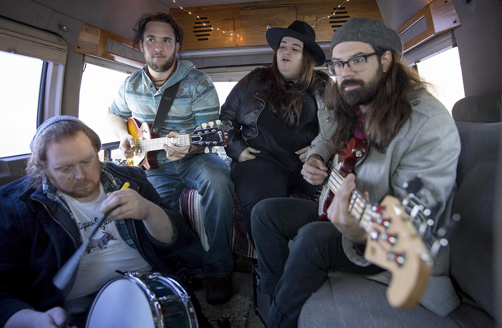 """Julie Rhodes and her band play """"Holes"""" in their tour bus. (Robin Lubbock/WBUR)"""