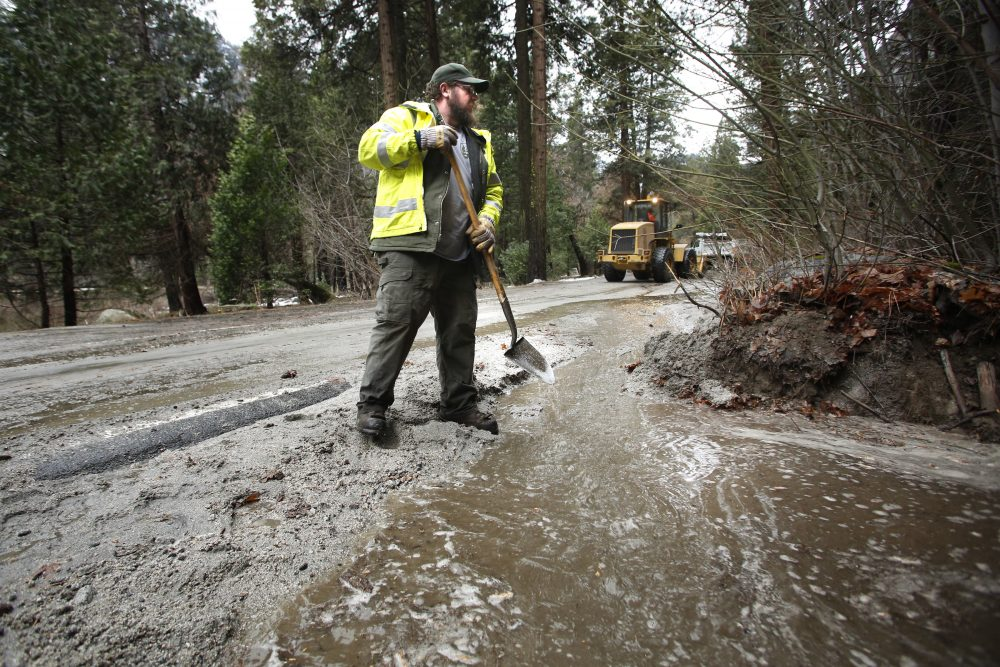 Road crew member Kevin Connor helps clean up state route 140 near the Merced River in a closed off Yosemite National Park, Calif., Sunday, Jan. 7, 2016. (Gary Kazanjian/AP)