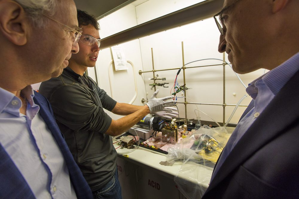 Harvard graduate student Andrew Wong, center, demonstrates his lab prototype of an organic mega flow battery to professor Roy Gordon, left, and professor Michael Aziz. (Jesse Costa/WBUR)