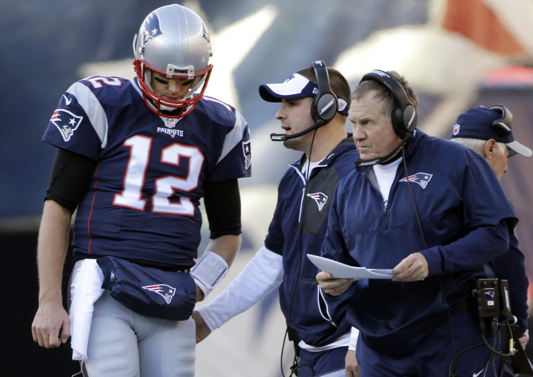 Patriots quarterback Tom Brady listens to offensive coordinator Josh McDaniels, middle, and head coach Bill Belichick during an NFL football game against the Los Angeles Rams in December. (Elise Amendola/AP)