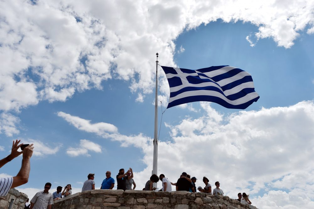 A man takes picture of a Greek flag atop the Acropolis archaeological site in August 2015. (Louisa Gouliamaki/AFP/Getty Images)