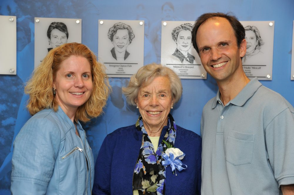 Mount Holyoke athletic director Lori Hendricks (left), Imogene Fish and associate professor of environmental studies Tim Farnham stand in front of Fish's plaque at the 2013 Mount Holyoke College Athletic Hall of Fame induction ceremony. (Courtesy of RJB Sports Photography)