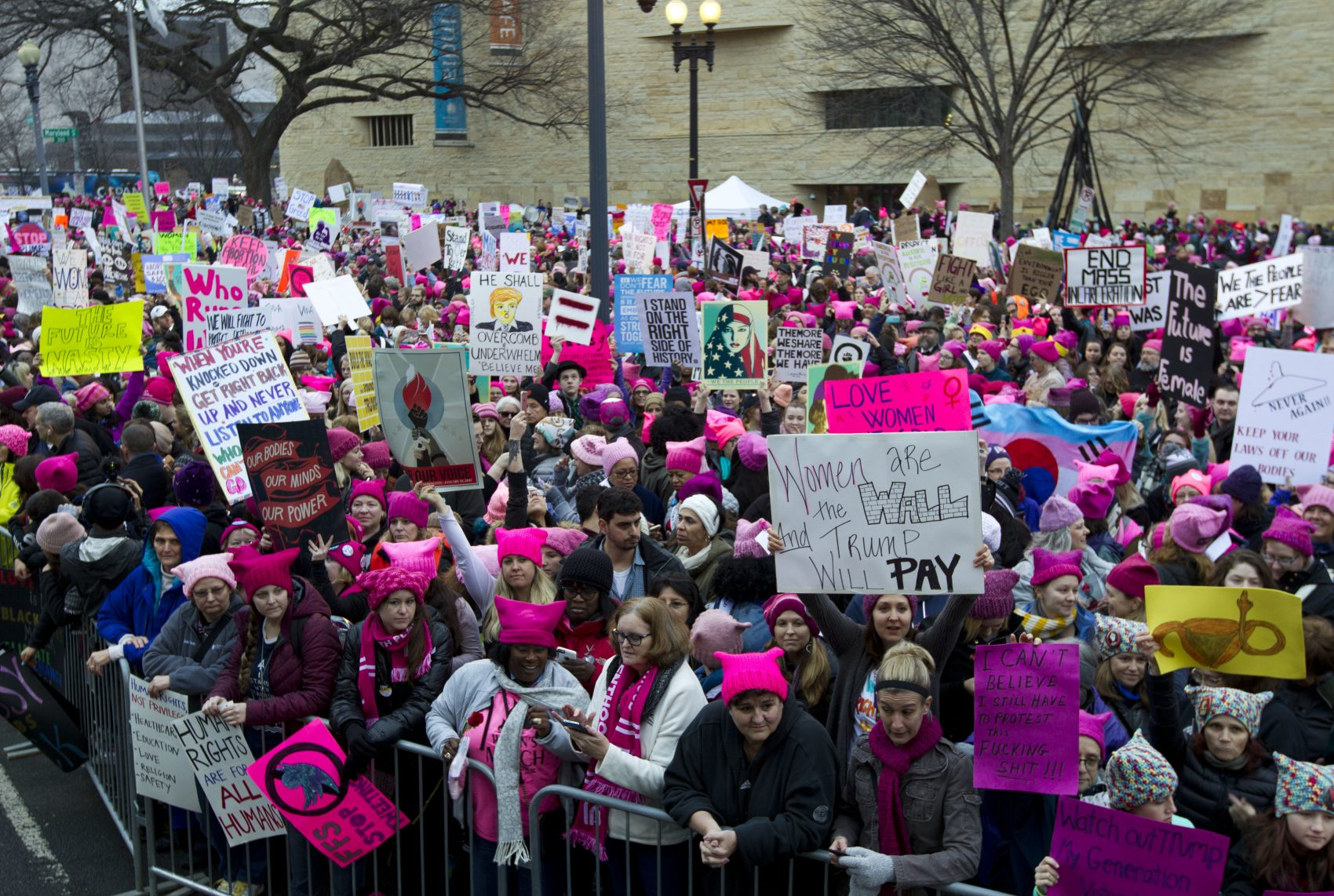 Women with bright pink hats and signs gathered in D.C. early on Saturday. (Jose Luis Magana/AP)