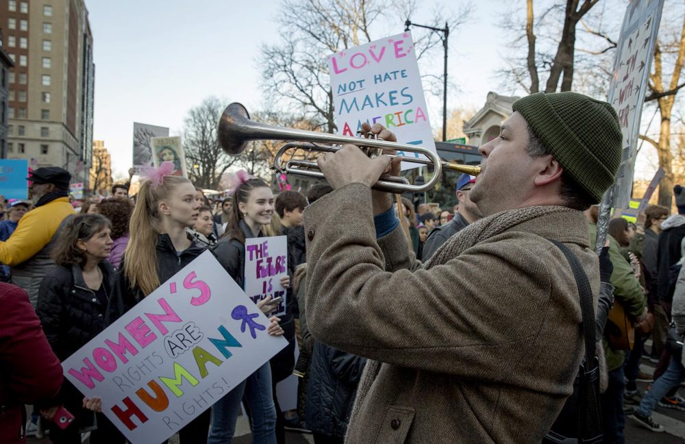 "Jason McCool plays ""We Shall Overcome"" on his trumpet as marchers walk by the Boston Public Garden. (Robin Lubbock/WBUR)"