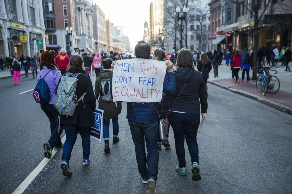 "A man held a sign that read: ""Men of quality don't fear equality."" (Jesse Costa/WBUR)"