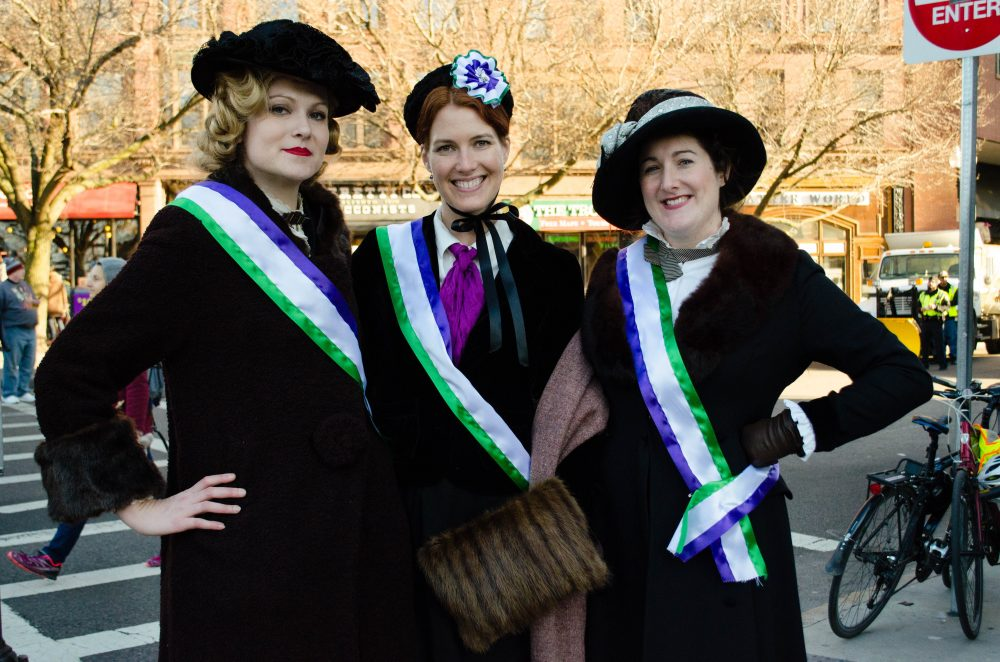 """Vintage enthusiasts"" Sarah Kruse, from Providence, Laura Grzybowski, of Newton, and Brooke Steinhauser, of Amherst, dressed as suffragettes for the march. (Elizabeth Gillis/WBUR)"