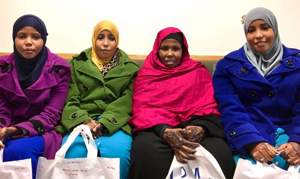 The Ahmed family waits for assistance as they resettle in Lowell. From left to right, Asha Ahmed, 22, her sister, Muna, 24, their mother, Fatuma Nur, 57, and Hawo, 24. (Shannon Dooling/WBUR)