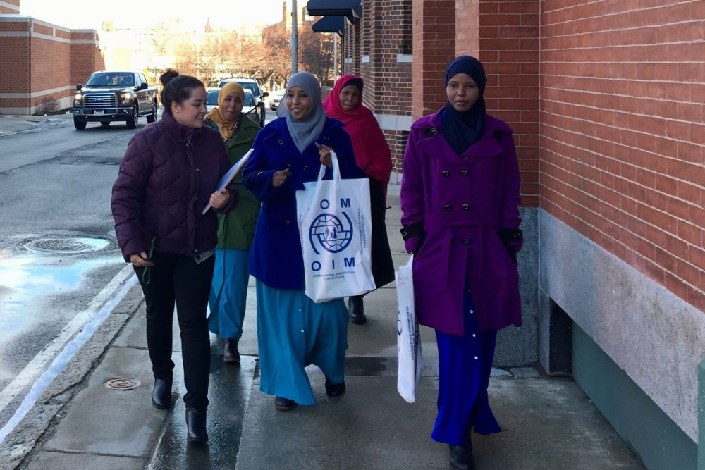 A volunteer from the International Institute of New England, far left, helps the Ahmed family get to the Department of Transitional Assistance's Lowell office. (Shannon Dooling/WBUR)