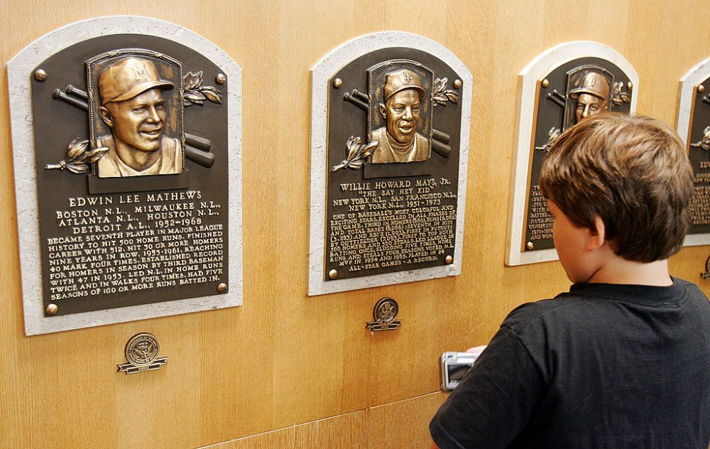 A young baseball fan looks at plaques of players inducted into the National Baseball Hall of Fame and Museum on July 26, 2008 in Cooperstown, N.Y. (Jim McIsaac/Getty Images)