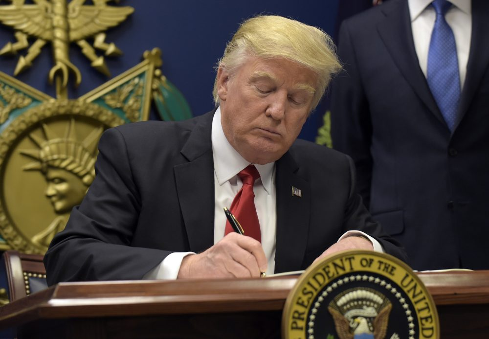 """President Donald Trump signs an executive order on """"extreme vetting"""" during an event at the Pentagon Friday. (Susan Walsh/AP)"""