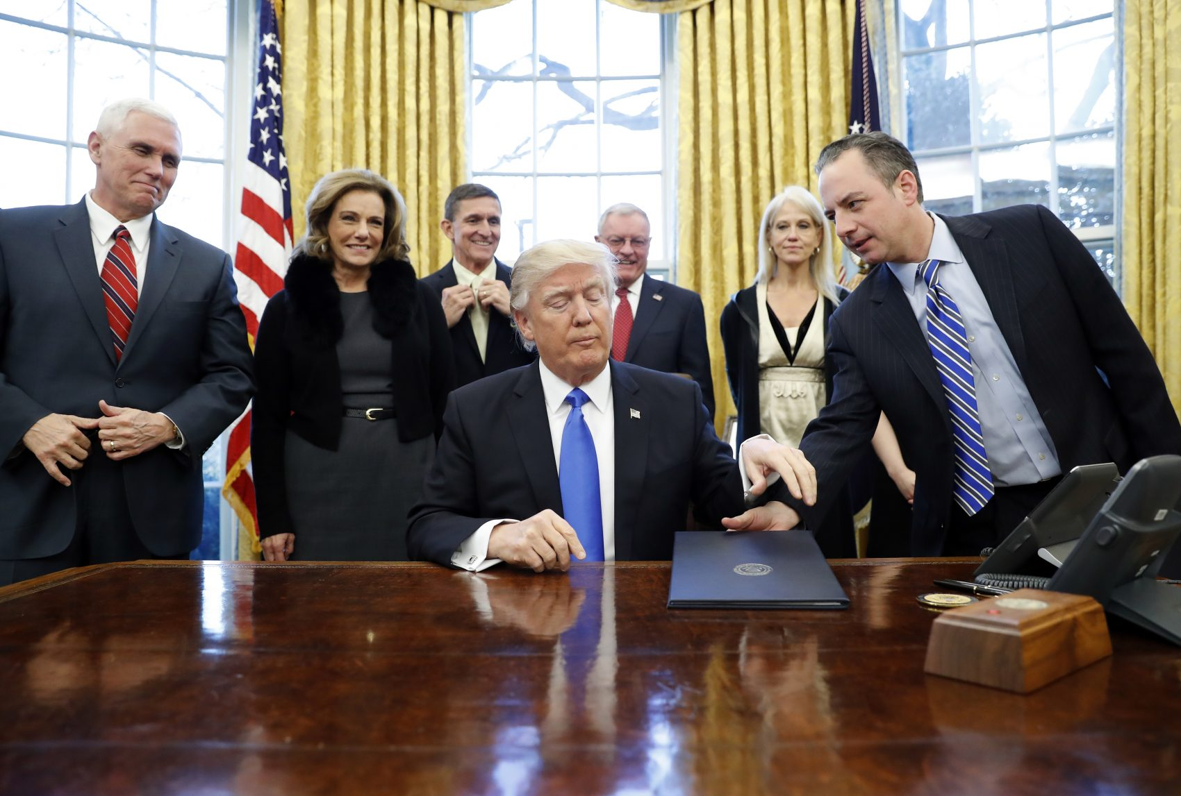 President Donald Trump is handed an Executive Order to sign by White House Chief of Staff Reince Priebus with Vice President Mike Pence and others in the Oval Office Saturday. (Alex Brandon/AP)