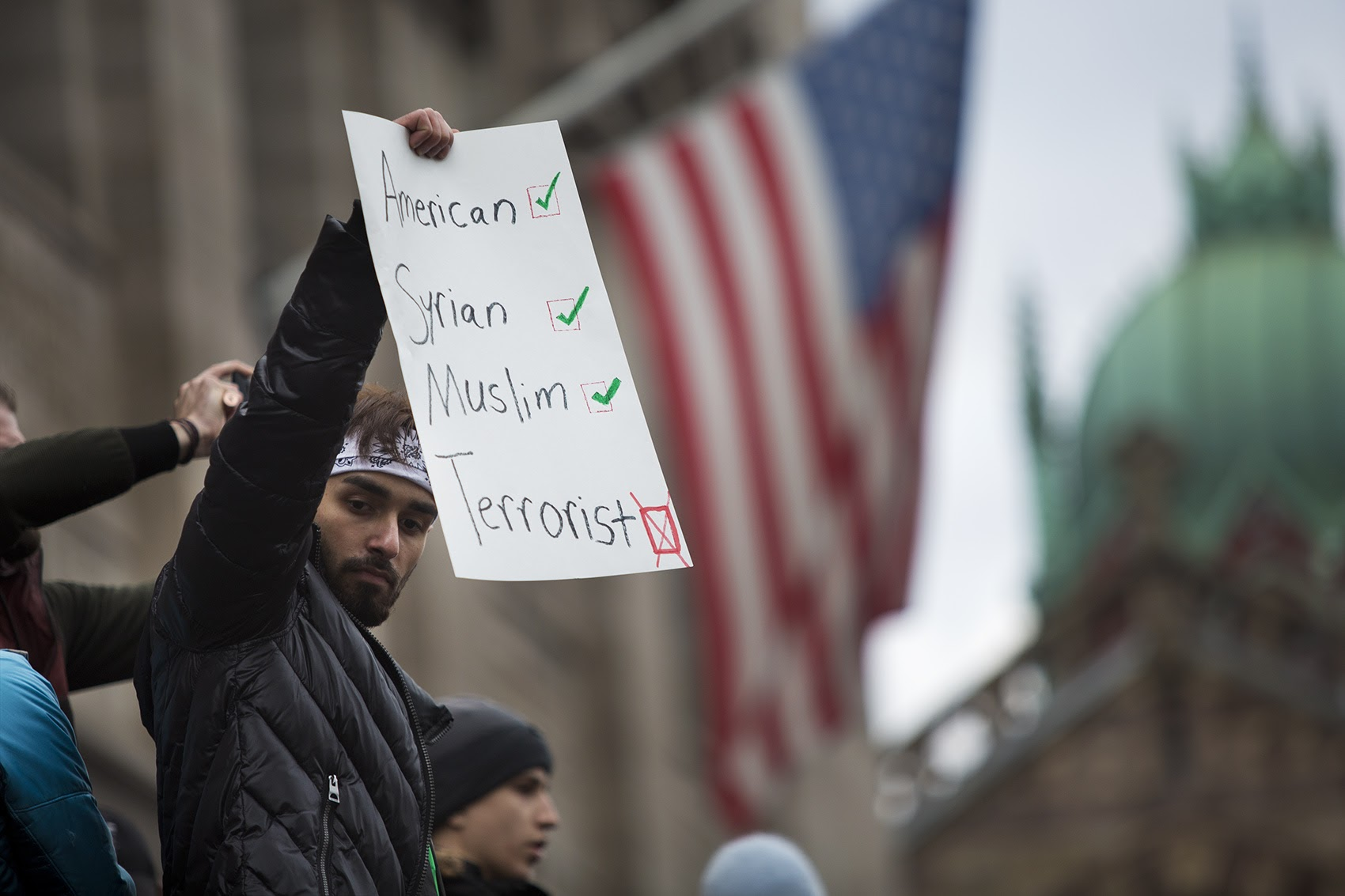 A demonstrator held a sign in front of the Boston Public Library Sunday. (Jesse Costa/WBUR)