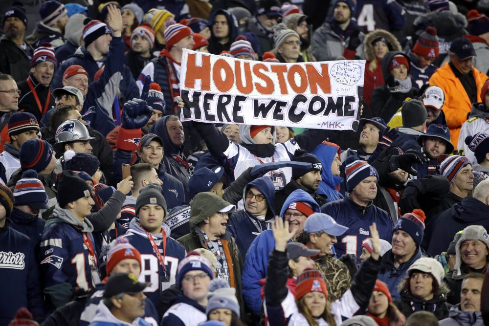 A New England Patriots fan holds a sign referring to the team's upcoming trip to Houston to face the Atlanta Falcons in Super Bowl LI. (Elise Amendola/AP)
