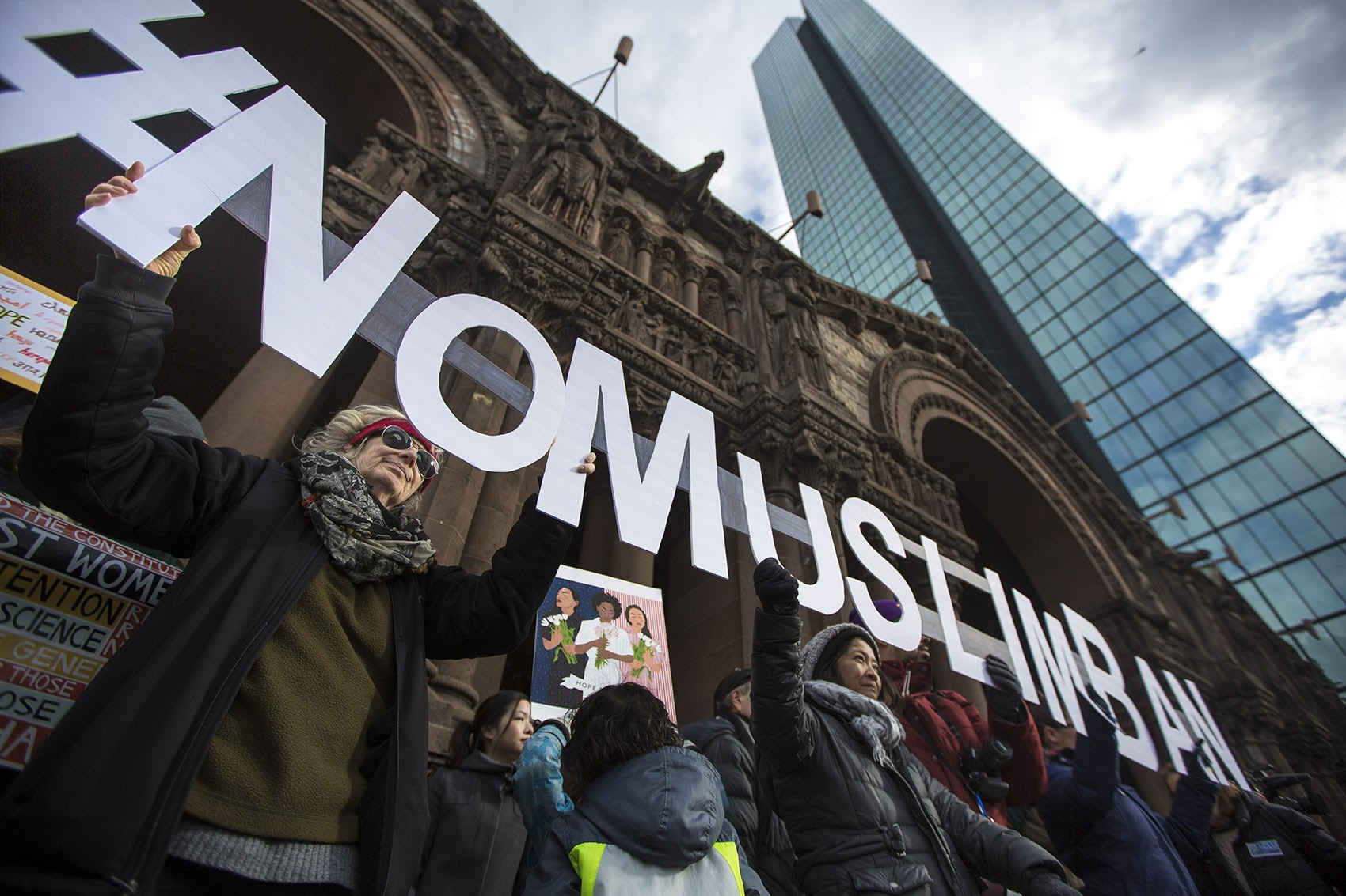 "A string of protesters in front of Trinity Church held letters spelling out ""#NOMUSLIMBAN."" (Jesse Costa/WBUR)"