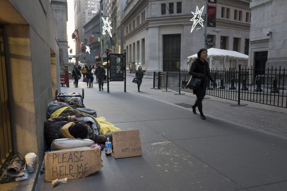 A homeless man sleeps on Wall Street near the New York Stock Exchange, Wednesday, Dec. 21, 2016. (Mark Lennihan/AP)