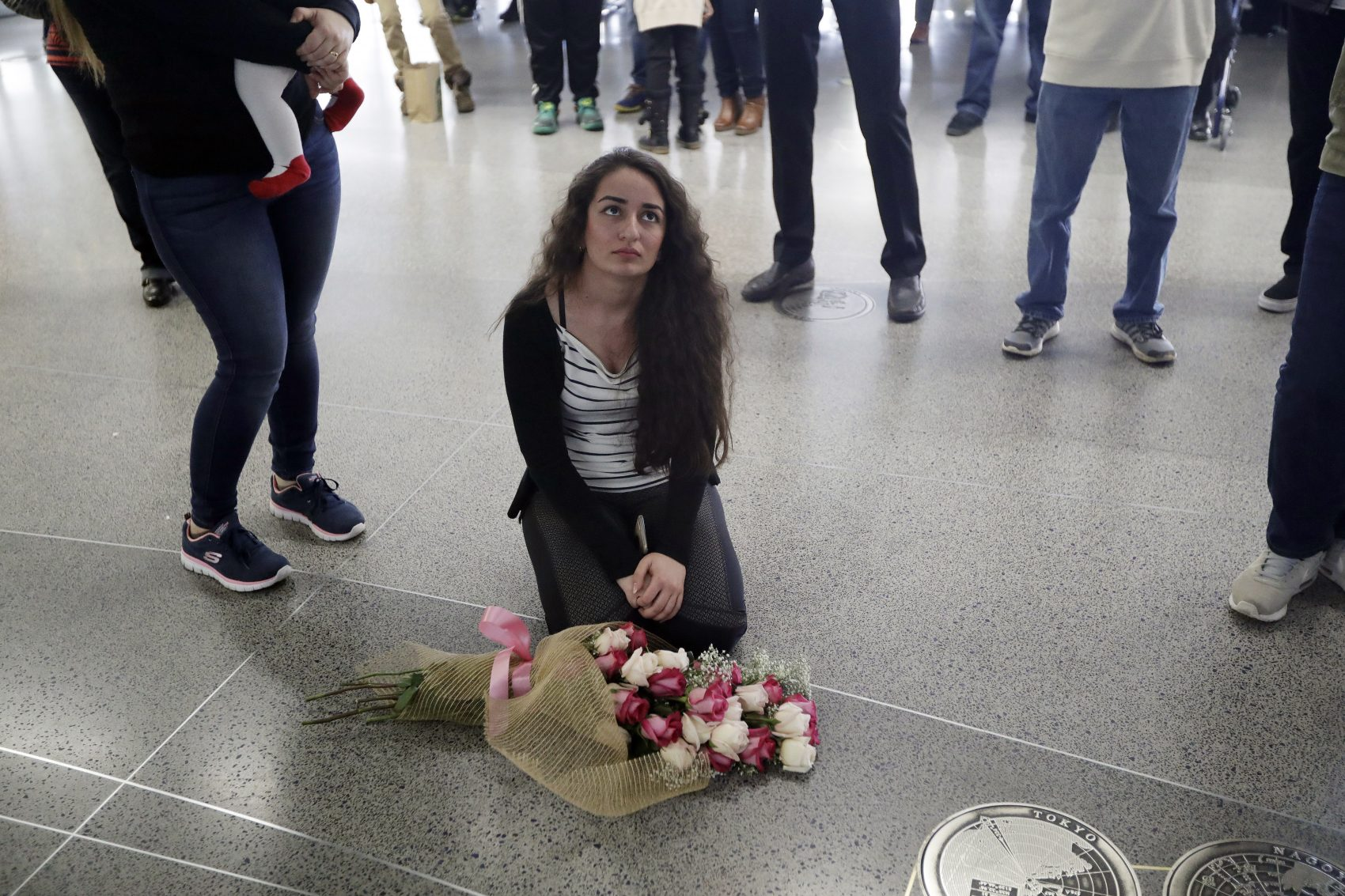 The crisis over President Trump's immigration ban, writes John Tirman, has emerged from its unconstitutionality as well as from the way the government has flaunted court orders blocking parts of the ban. Pictured: Reem Alrubaye, of Fremont, Calif., places flowers on the floor as she waits for her mother Mason Jadoaa to return from a visit to Baghdad, Iraq, at San Francisco International Airport, Monday, Jan. 30, 2017. (Marcio Jose Sanchez/AP)