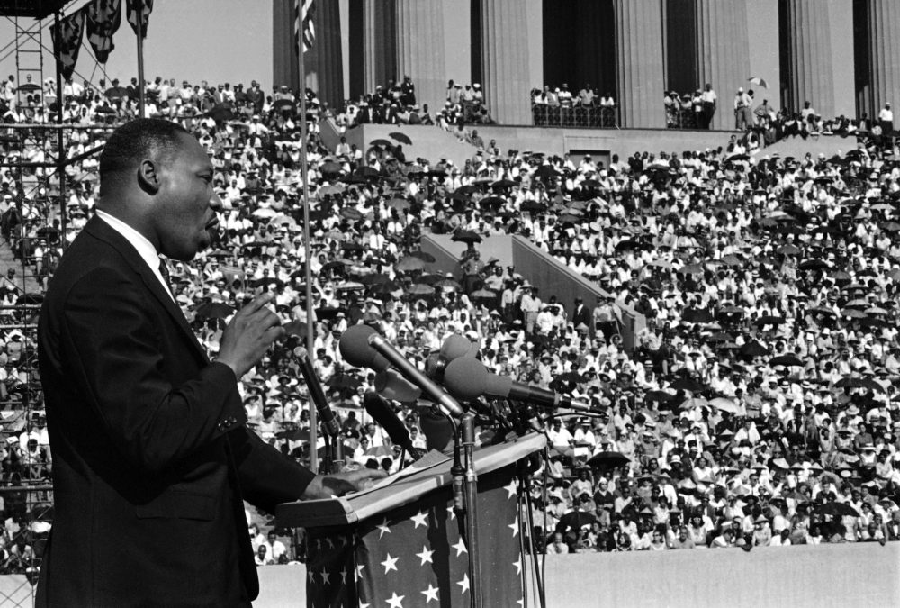 """The Rev. Martin Luther King addresses a crowd estimated at 70,000 at a civil rights rally in Chicago's Soldier Field June 21, 1964. King told the rally that congressional approval of civil rights legislation heralds """"the dawn of a new hope for the Negro."""" (Charles E. Knoblock/AP)"""