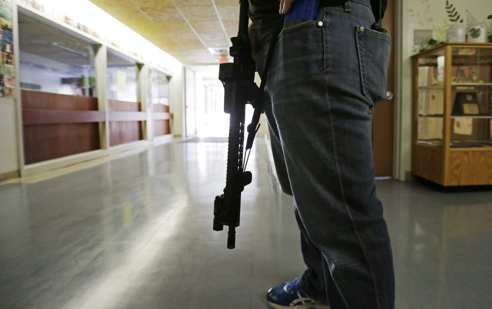 Lt. Greg Gallant, of the Methuen Police Department, portrays an active shooter as he roams the halls of a school with an assault rifle, loaded with dummy rounds, during a 2014 demonstration. (Charles Krupa/AP)