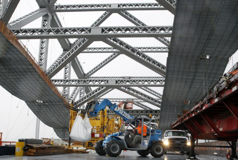 In this Nov. 15, 2016, file photo, a worker lifts materials as construction continues on the new roadway deck of the Bayonne Bridge in Bayonne, N.J. Even as they maneuver for a share of the $1 trillion in spending President-elect Donald Trump promised to rebuild America's roads, bridges and airports, lobbyists for transportation and utility industries are beginning to wonder whether Trump really meant what he said. From the day he formally entered the presidential race to the moment he declared victory, Trump pledged to rebuild the nation's aging and inadequate infrastructure. (Mel Evans/AP)