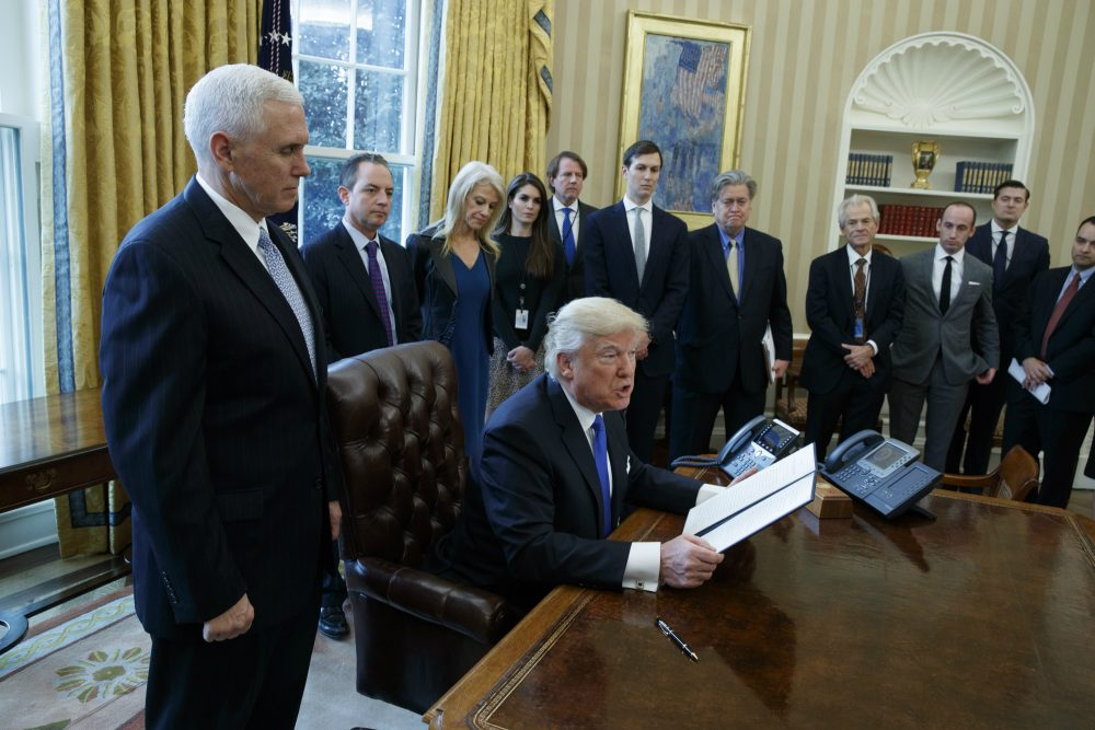 Trump's incoming White House team of policy staff and advisors will pale to that of his predecessors, literally, writes Kevin C. Peterson. For many, it will represent a step backward from hard-earned racial and gender progress. Pictured: President Donald Trump, accompanied by Vice President Mike Pence, and staff, talks with reporters in the Oval Office of the White House in Washington, Tuesday, Jan. 24, 2017, before signing an executive order on the Dakota Access pipeline. (Evan Vucci/AP)