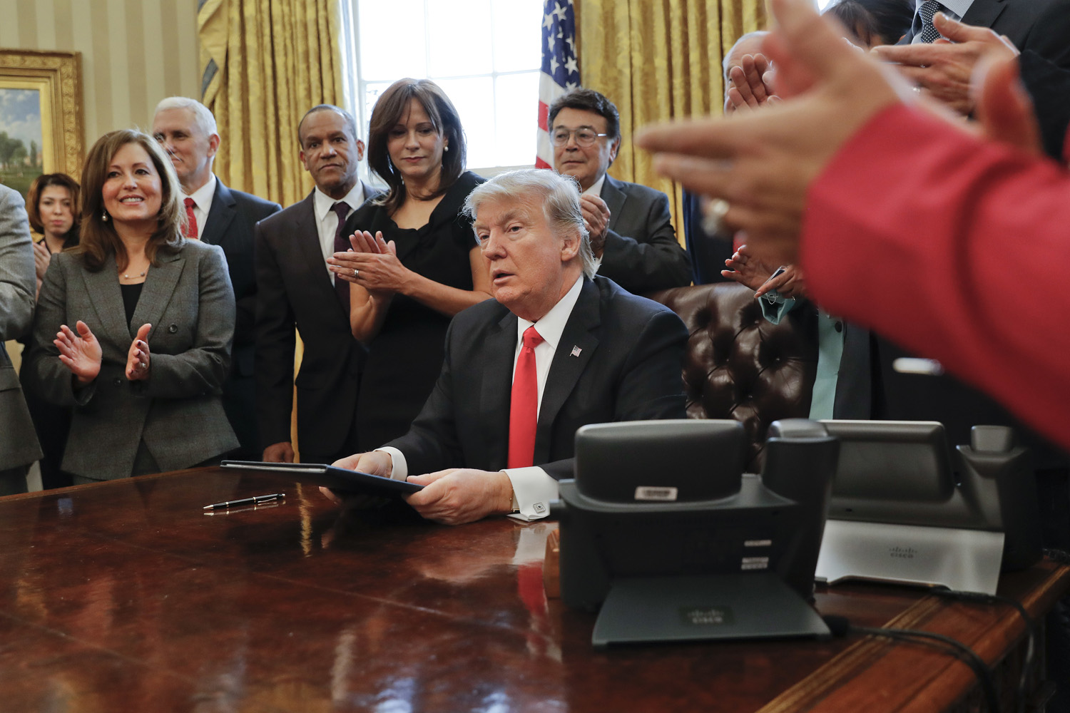 Small business leaders applaud President Donald Trump after he signed an executive order in the Oval Office of the White House in Washington, DC. (Pablo Martinez Monsivais/AP)