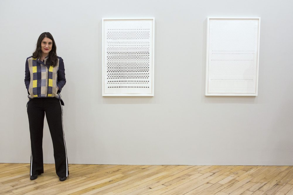 "Artist Carly Glovinski stands next to her works ""DARKERearlier,"" left, and ""LIGHTERlater"" on display at the Carroll and Sons gallery in the South End. (Jesse Costa/WBUR)"