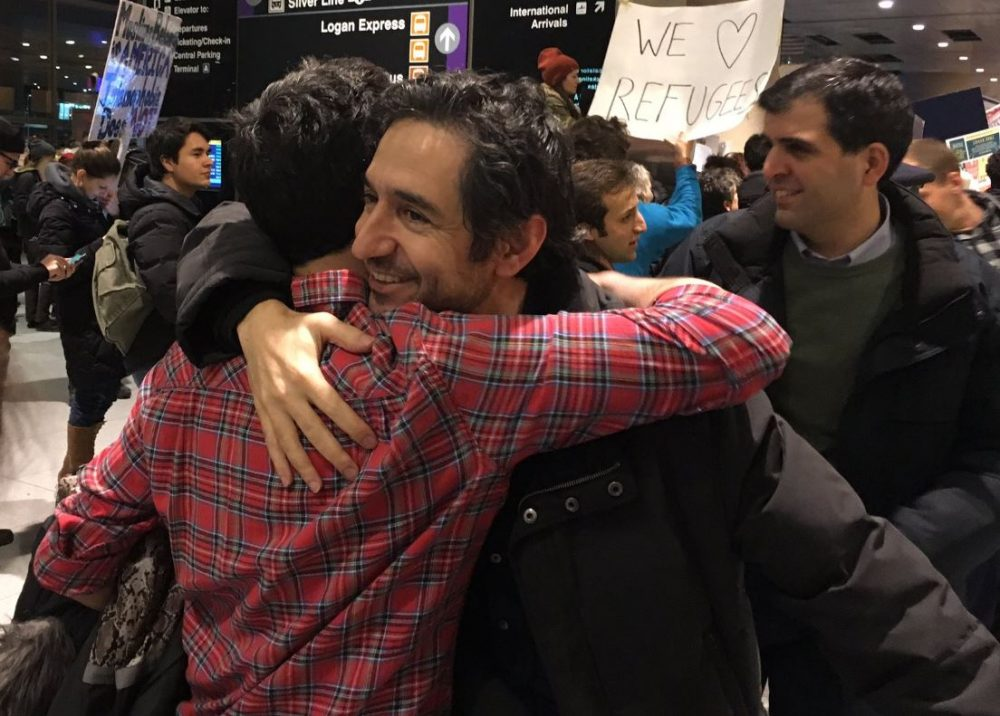Mazdak Tootkaboni, a UMass Dartmouth professor from Iran, greets his family after several hours being held at Logan Airport. He was one of the petitioners on the temporary restraining order. (Shannon Dooling/WBUR)