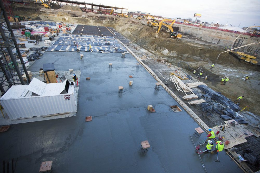 Workers smooth out freshly laid concrete for a basement parking lot of the Wynn Boston Harbor Casino in Everett. (Jesse Costa/WBUR)