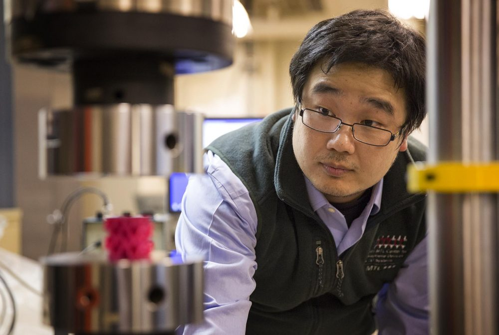MIT research scientist Zhao Qin sets up an experiment in the lab. He was on the team that discovered a gyroid structure that makes materials more resilient. (Robin Lubbock/WBUR)