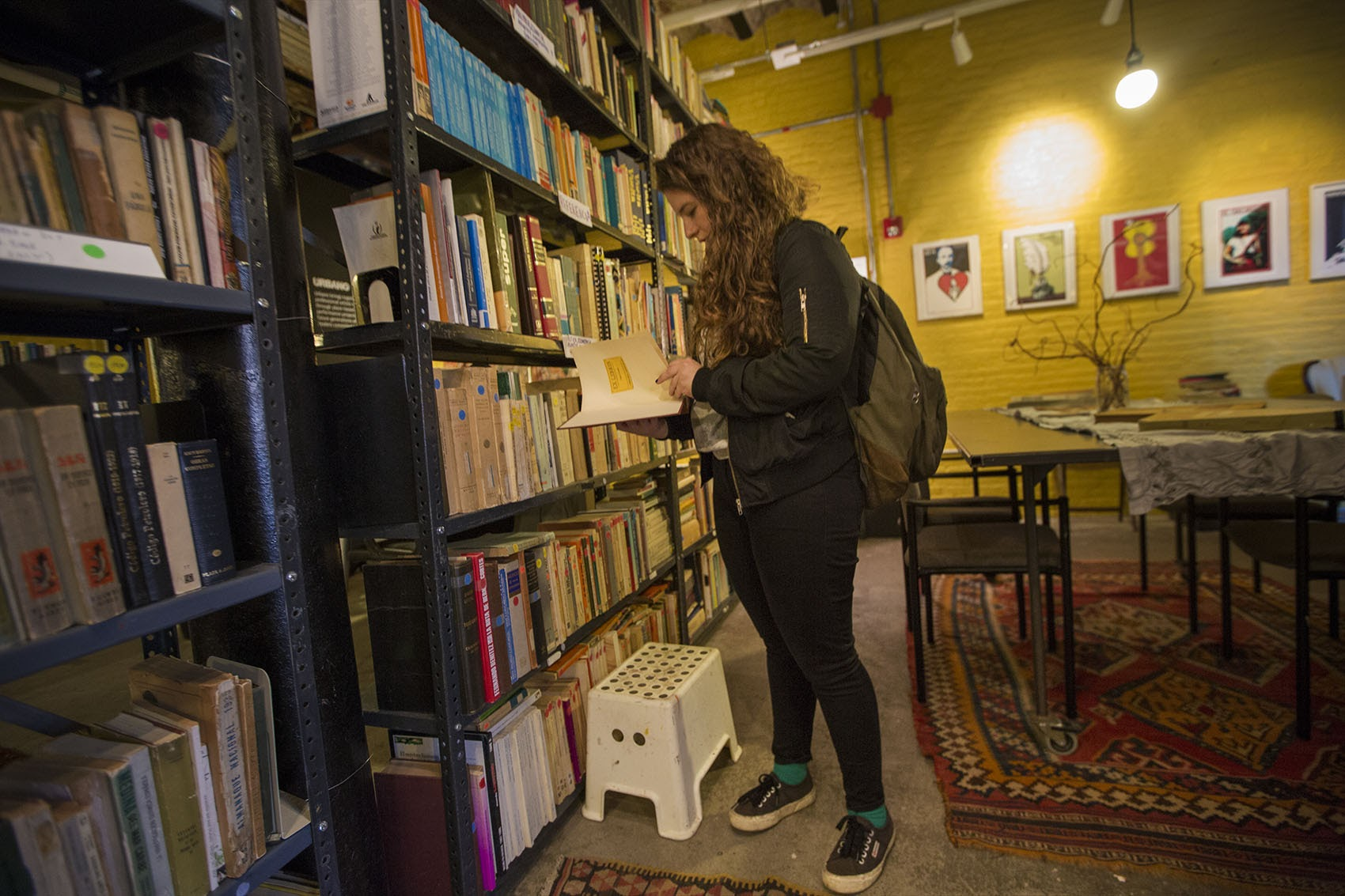 Tovia Siegel, of Watertown, looks at an encyclopedia from the reference section of Librería Donceles. She just returned from Chile after working there for six months as a teacher.  (Jesse Costa/WBUR)