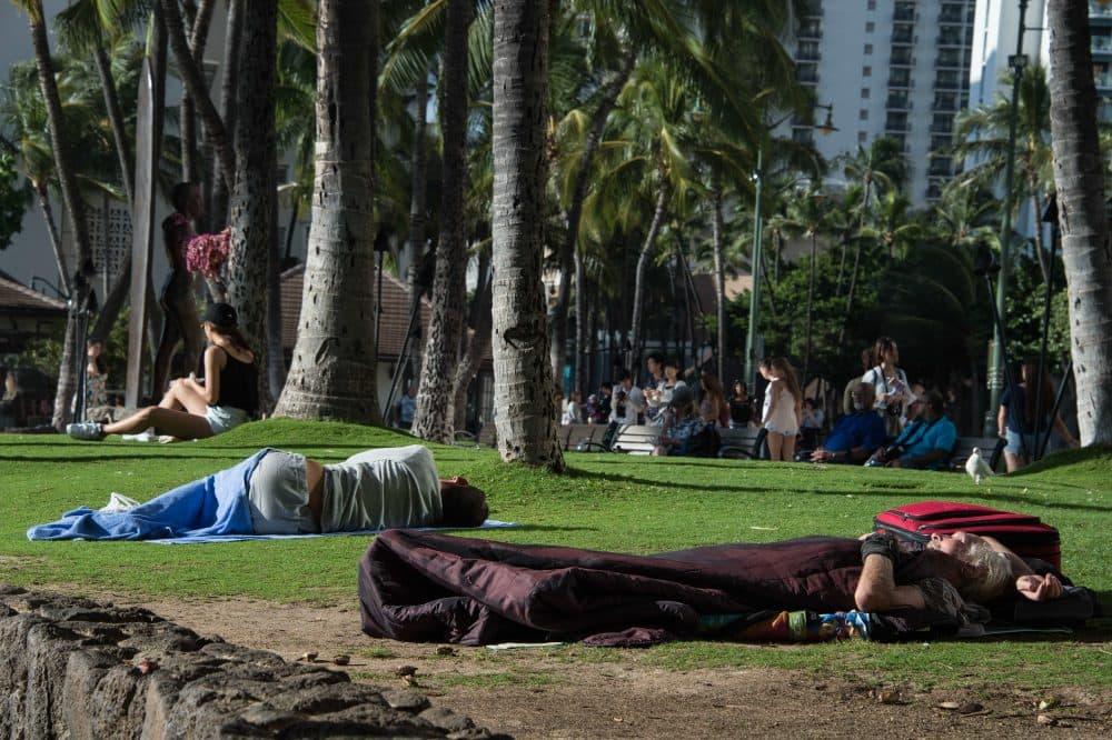 Homeless people sleep in a park off the beach in the Waikiki neighborhood of Honolulu, Hawaii, on Dec. 17, 2016. (Nicholas Kamm/AFP/Getty Images)