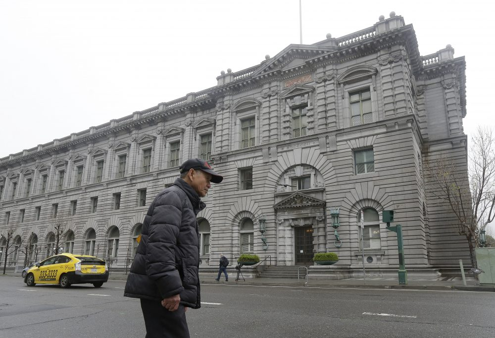 A man walks outside of the 9th U.S. Circuit Court of Appeals in San Francisco, Tuesday, Feb. 7, 2017. President Donald Trump's travel ban faced its biggest legal test yet Tuesday as a panel of federal judges prepared to hear arguments from the administration and its opponents about two fundamentally divergent views of the executive branch and the court system. (Jeff Chiu/AP)