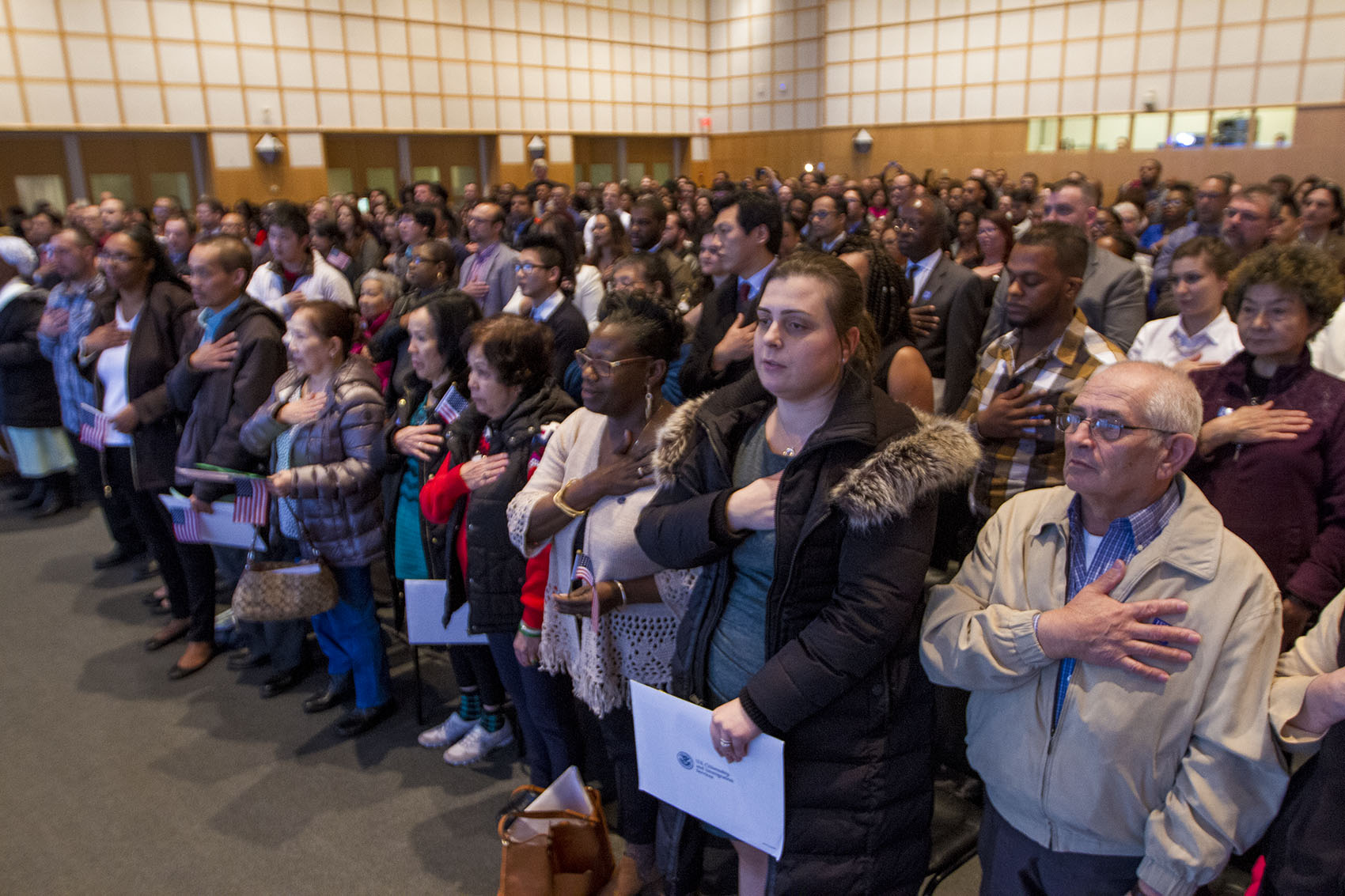 New citizens recite the Pledge Of Allegiance during a ceremony at the Boston's JFK Library on Thursday. (Jesse Costa/WBUR)