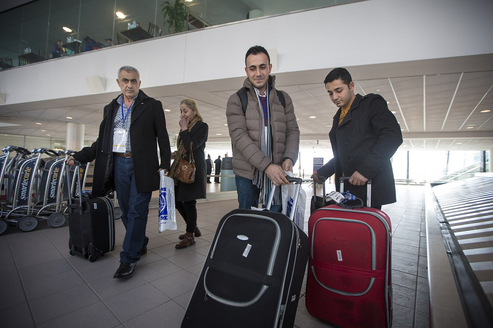 From left to right, Mohamad, Zeinab, Rashid  and Ahmad Mahmoud arrive at Manchester-Boston Regional Airport in New Hampshire. (Jesse Costa/WBUR)