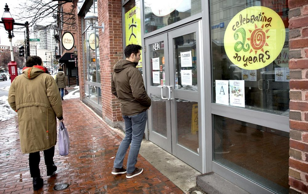 "Jake Shuman, 23, reads a sign on the door of Anna's Taqueria on Cambridge Street in Boston. It says the restaurant is closed to support ""our employees desire to participate in the 'Day Without Immigrants.' "" (Robin Lubbock/WBUR)"