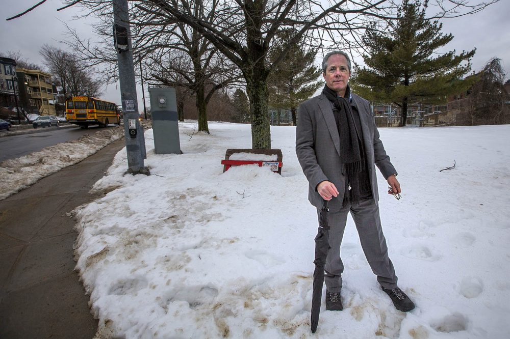 Bart Mitchell, CEO of Community Builders, Inc., stands on a parcel of land at the corner of Hyde Park Avenue and Ukraine Way in Jamaica Plain, where a 78-unit mixed-income housing development has been stalled. (Jesse Costa/WBUR)
