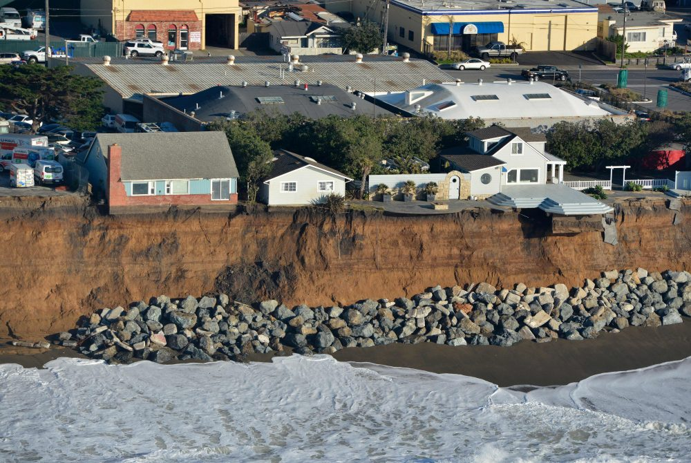 Houses hang over a cliff in Pacifica, Calif., in January 2016. Storms and powerful waves caused by El Nino have been intensifying erosion. (Josh Edelson/Getty Images)