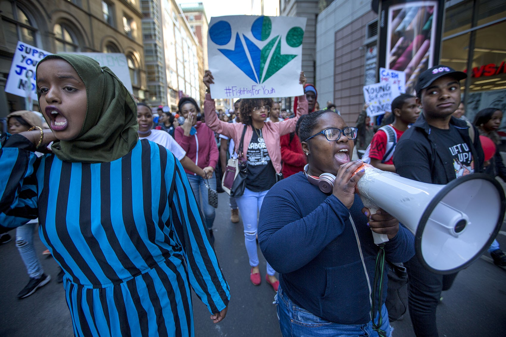 Youth activists march  through Downtown Crossing Thursday afternoon. They are calling on state and city leaders to fund more youth jobs and reform the juvenile justice system. (Jesse Costa/WBUR)