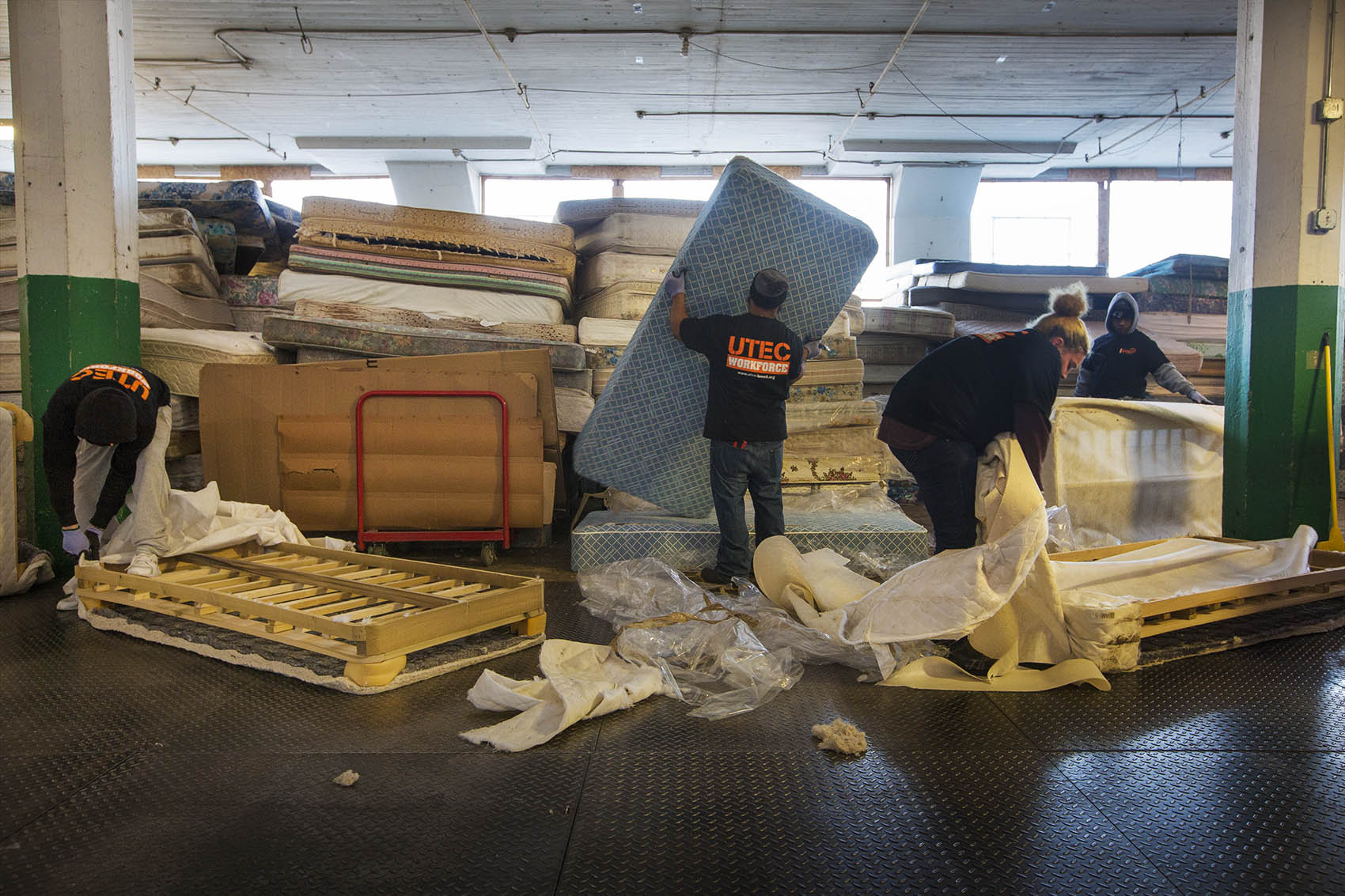 Workers at the UTEC mattress warehouse break down piles of mattresses. (Jesse Costa/WBUR)